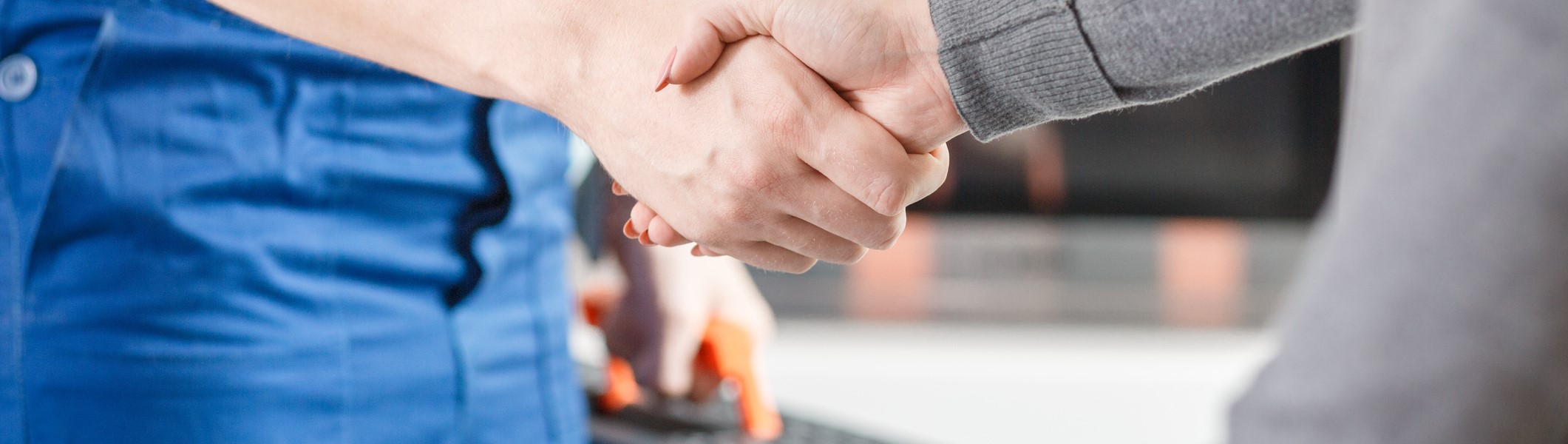 Man in blue jumpsuit holding toolbox and shaking hands with woman in gray sweater [906883676]