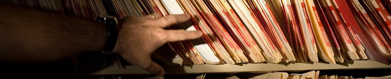 Mans hand reaching for shelf of medical records [172517207]