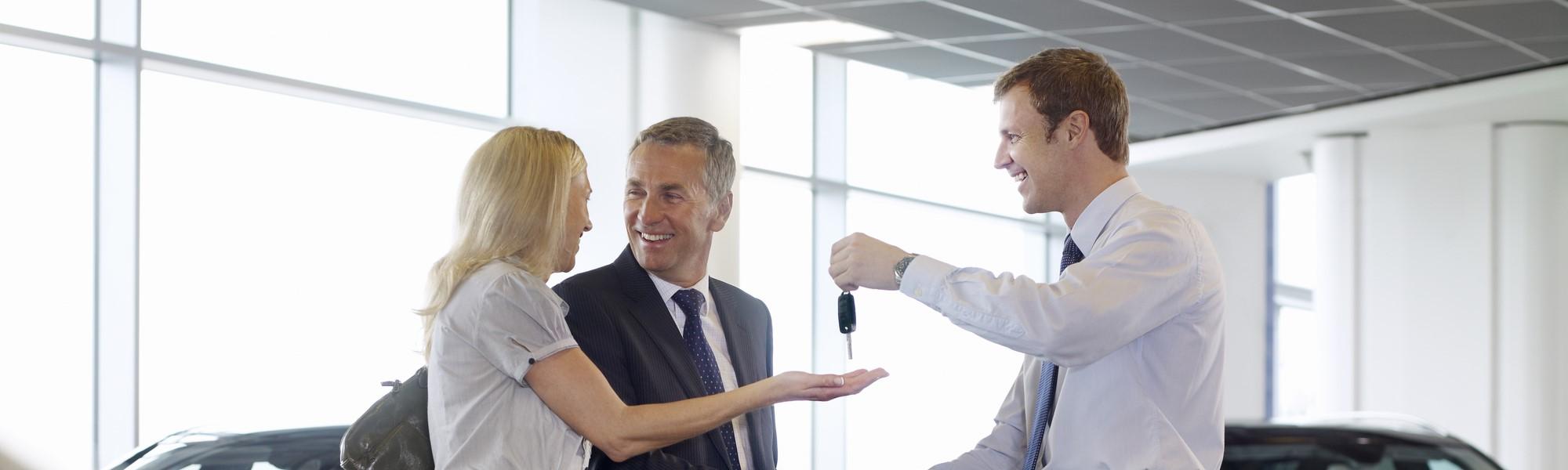 Salesman handing car keys to happy couple in showroom [108359372]