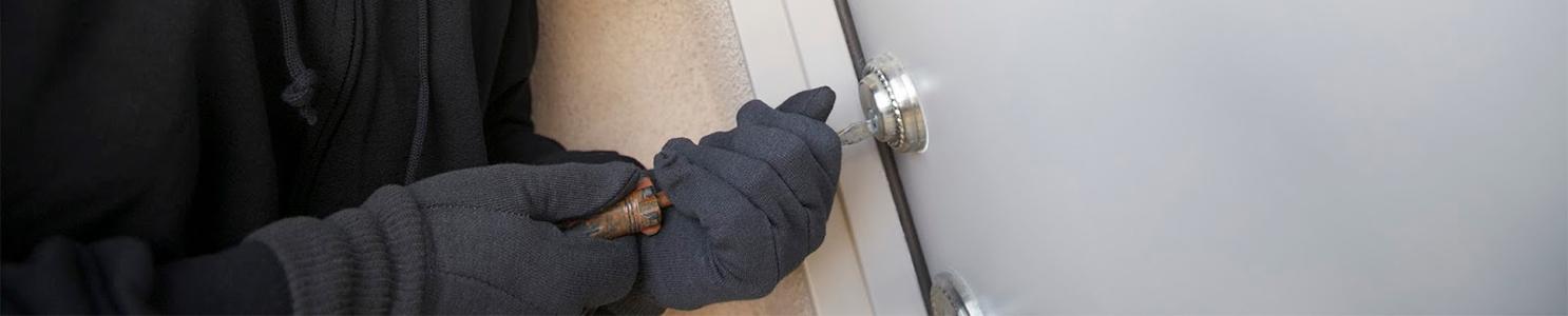 Burglar working on lock of front door [103577080]