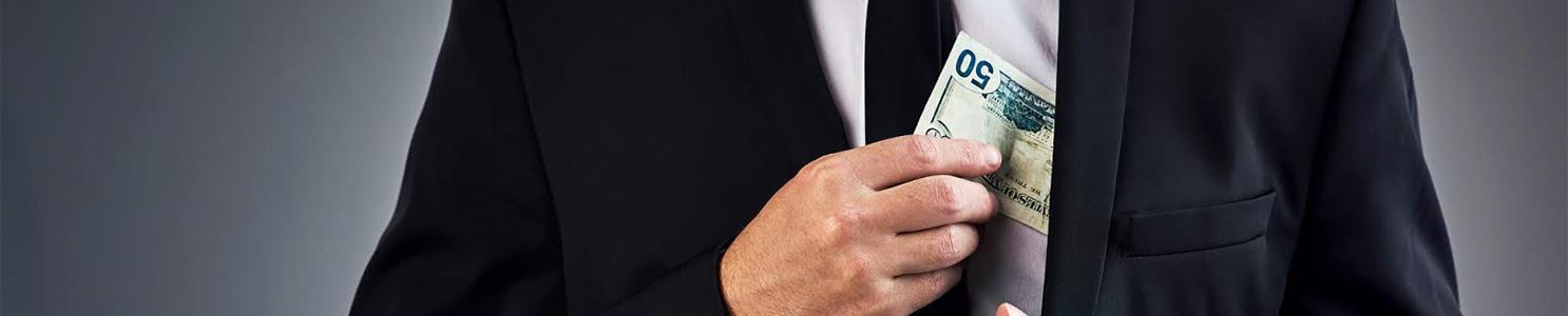 Businessman concealing money in suit jacket [840512460]